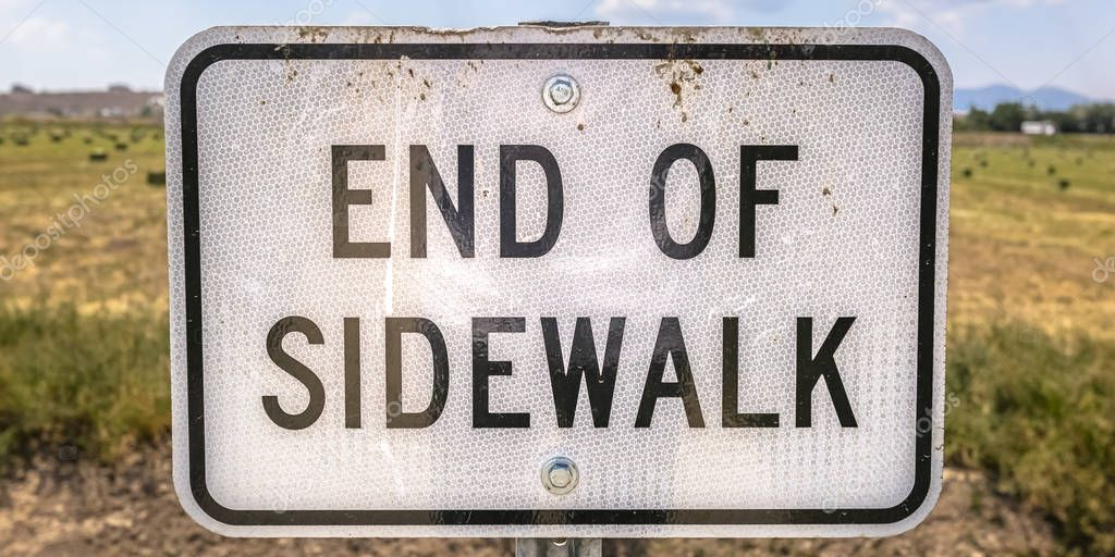 End of Sidewalk sign in front of a grassy terrain