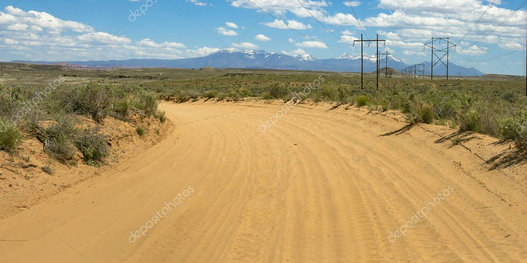 Curve sand road with power lines and mountain view