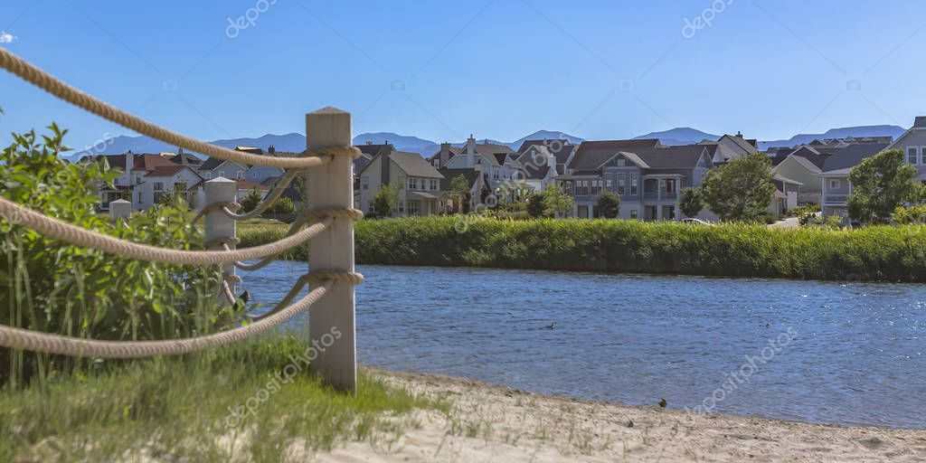 Lake with rope fence and houses on its sandy shore