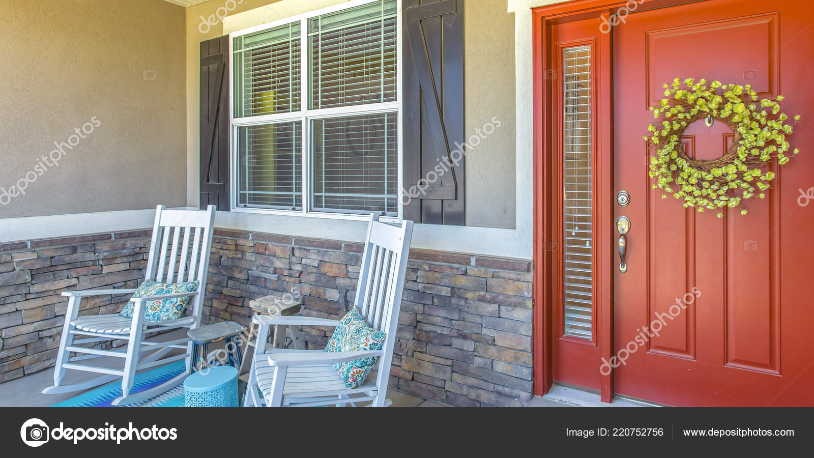 Red Front Door With Wreath And Chairs On Porch Stock Photo