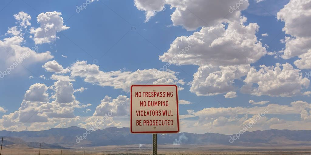 No trespassing sign against mountain and sky