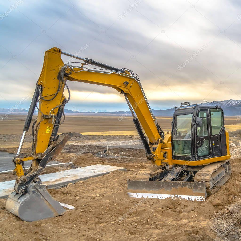 Excavator against mountain and sky in Utah Valley