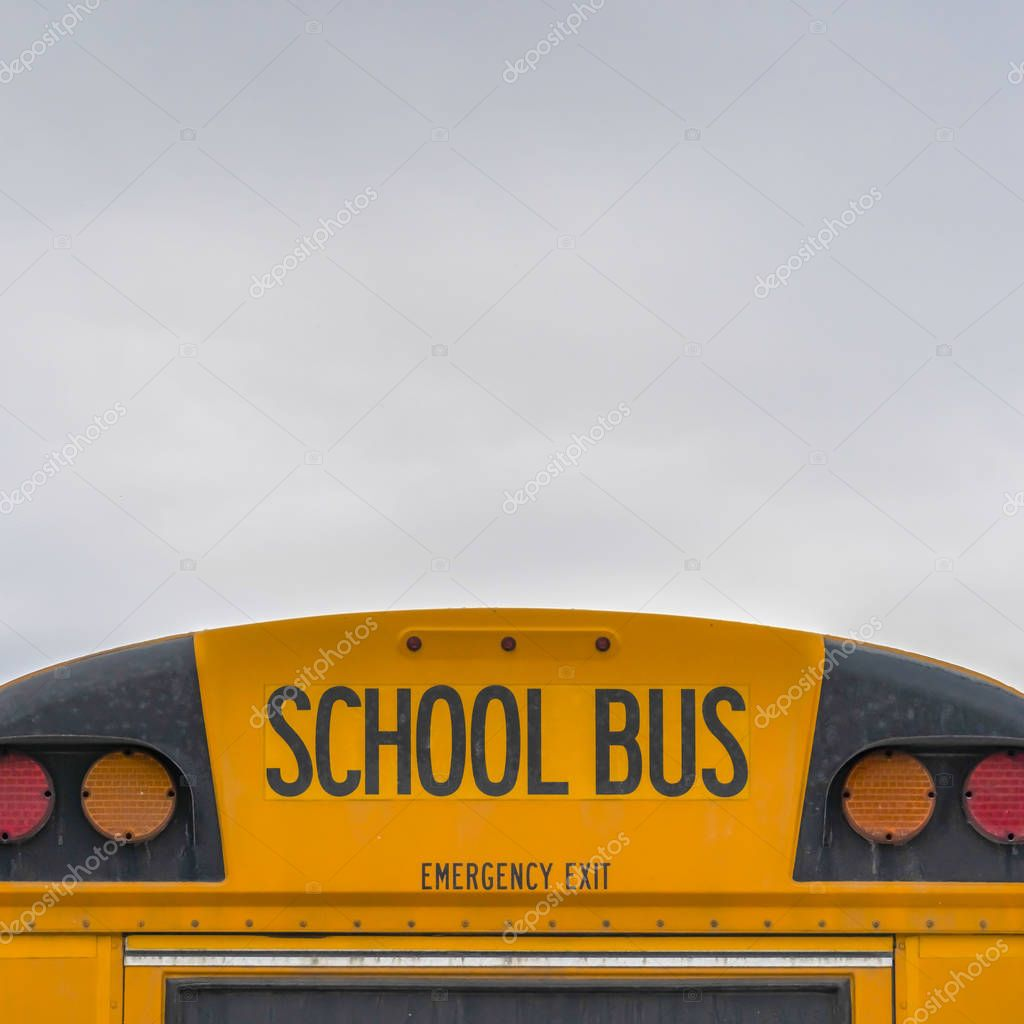 Square Rear of a yellow school bus with signal lights and emergency exit window
