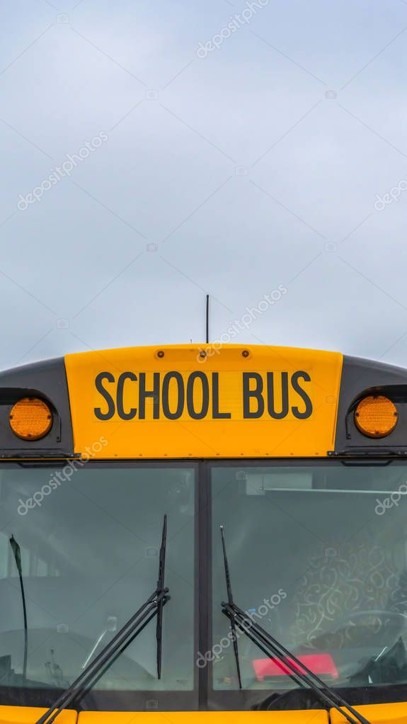 Vertical Front view of a yellow school bus with homes and cloudy sky in the background