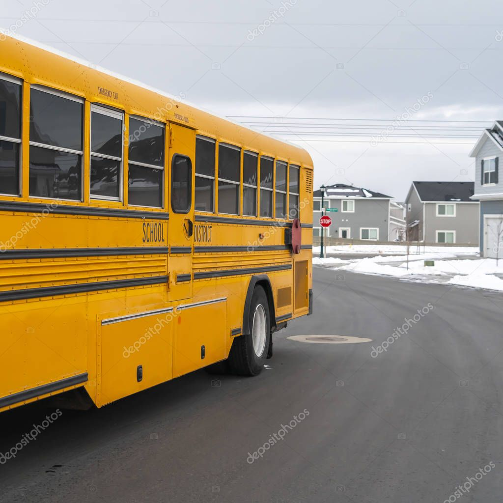 Clear Square Side view of a school bus on a road passing through snowy homes in winter