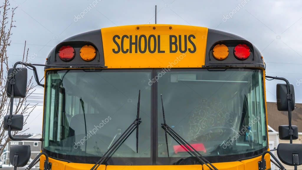 Clear Panorama Front view of a yellow school bus with homes and cloudy sky in the background