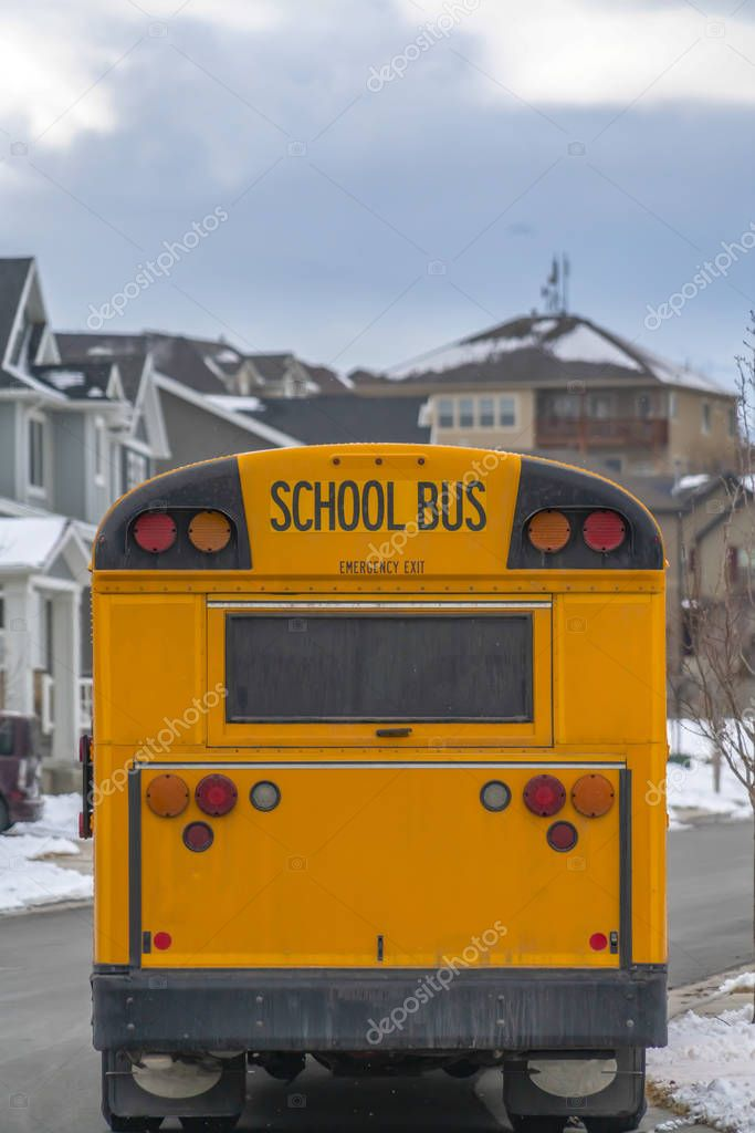 Rear of a yellow school bus against snowy homes and cloudy sky in winter