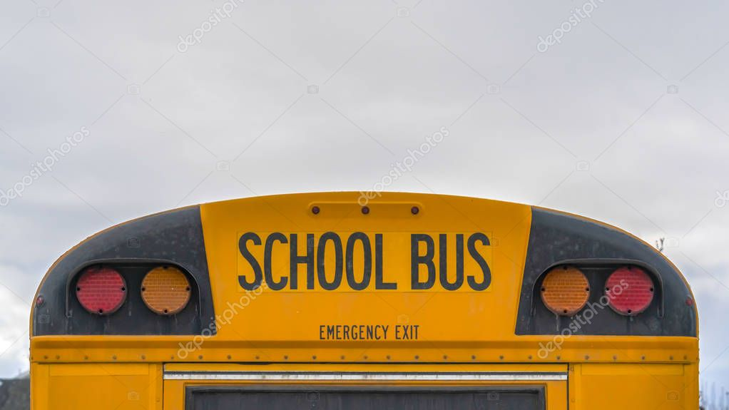 Clear Panorama Rear of a yellow school bus with signal lights and emergency exit window