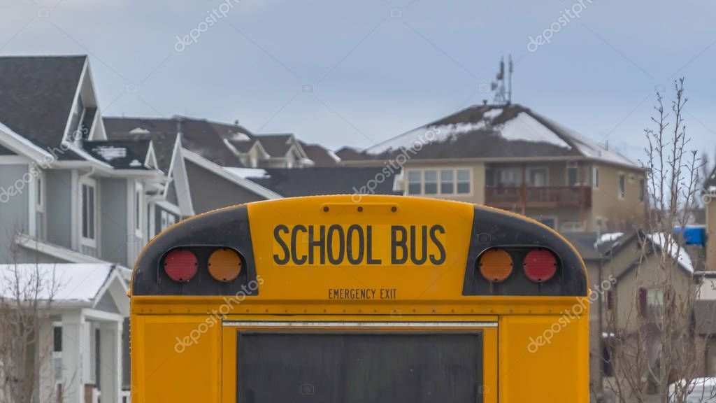 Clear Panorama Rear view of a yellow school bus with a window and several signal lights