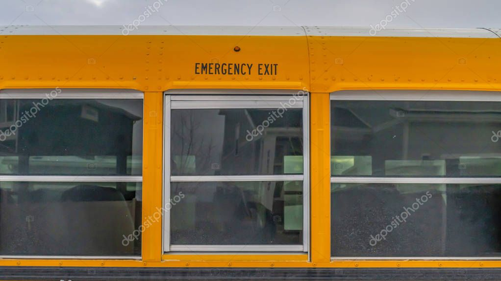 Clear Panorama CLose up of the exterior of a yellow school bus against cloudy sky
