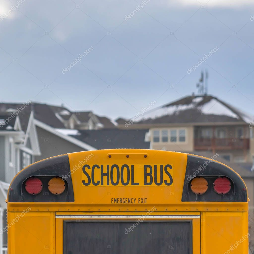 Square Yellow school bus with rectangular window and several signal lights at the rear