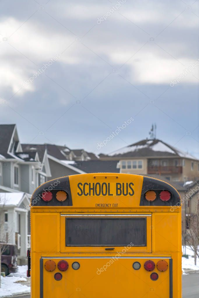 Yellow school bus with rectangular window and several signal lights at the rear