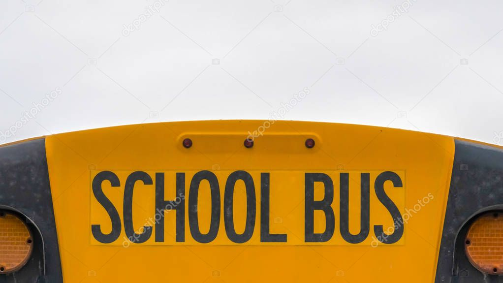 Panorama Close up of the back side of a yellow school bus against homes and cloudy sky