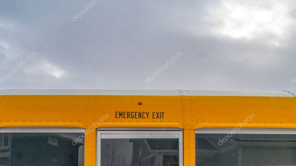 Panorama CLose up of the exterior of a yellow school bus against cloudy sky