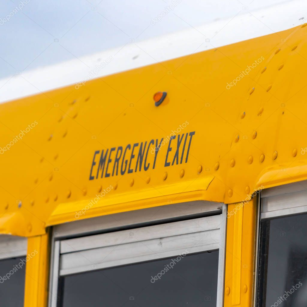 Clear Square Close up of the exterior of a yellow school bus with an Emergency Exit sign