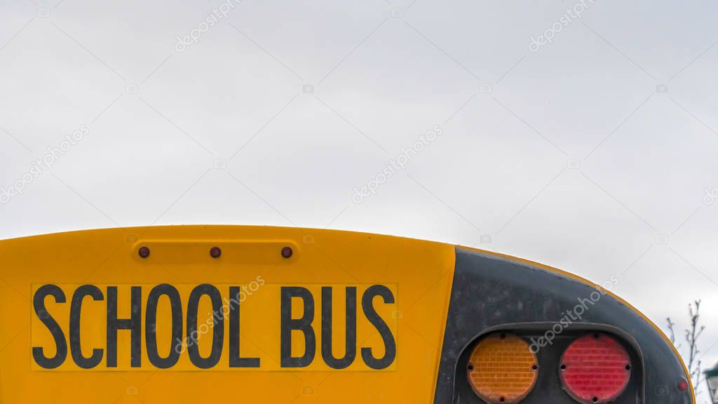 Clear Panorama Close up of the back side of a yellow school bus against homes and cloudy sky
