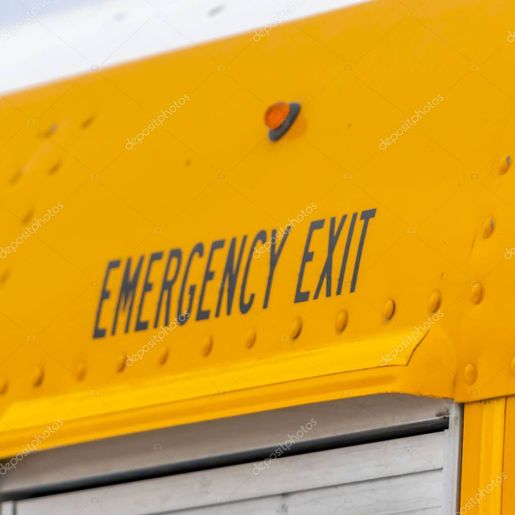 Square Close up of the exterior of a yellow school bus with an Emergency Exit sign
