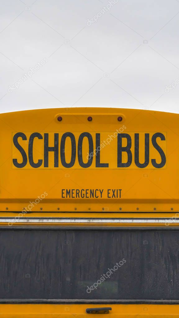 Vertical Close up of the back side of a yellow school bus against homes and cloudy sky