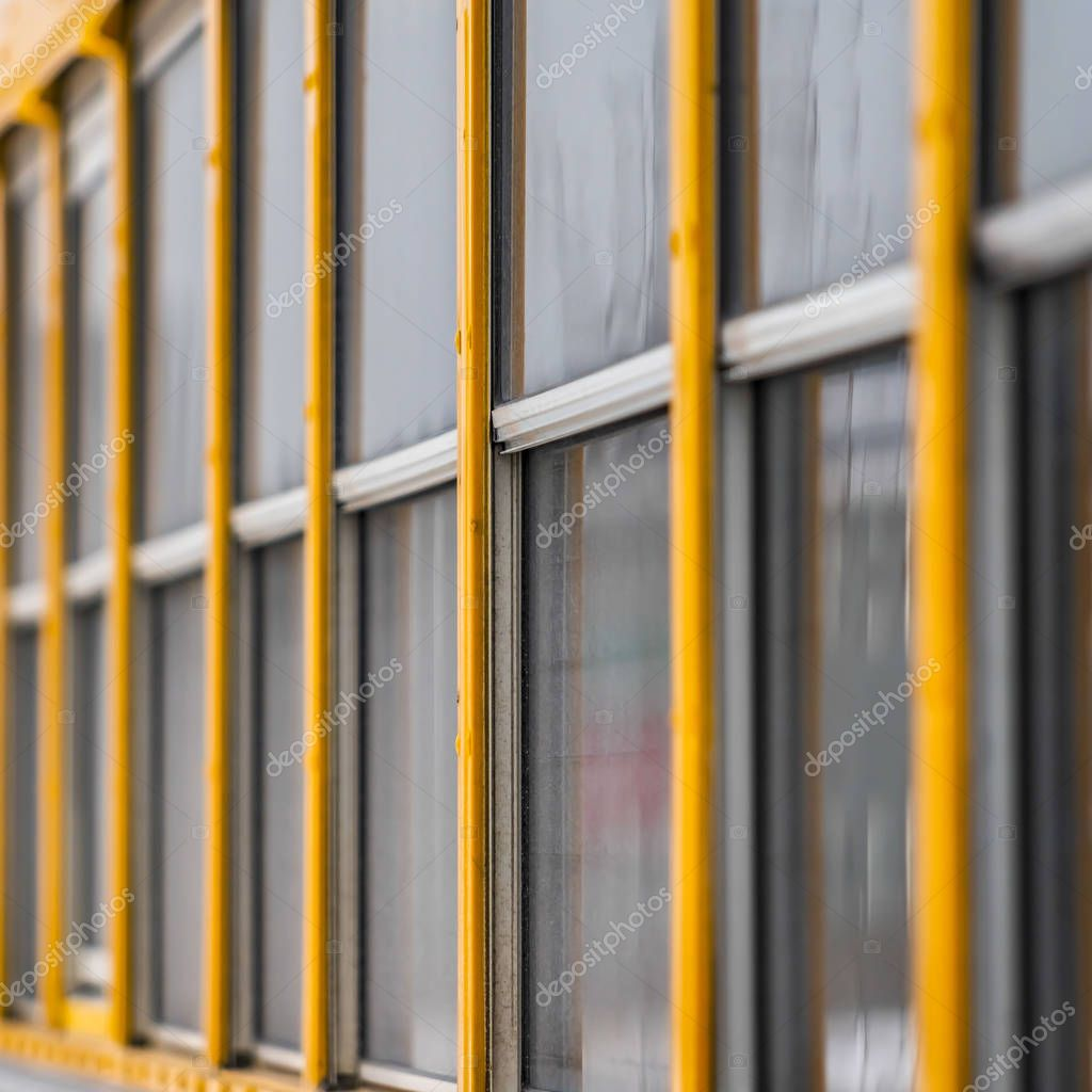 Square Exterior view of a yellow school bus with a close up on the glass windows