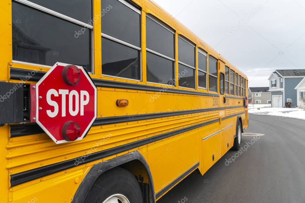 Exterior view of a yellow school bus with a red stop sign and signal lights