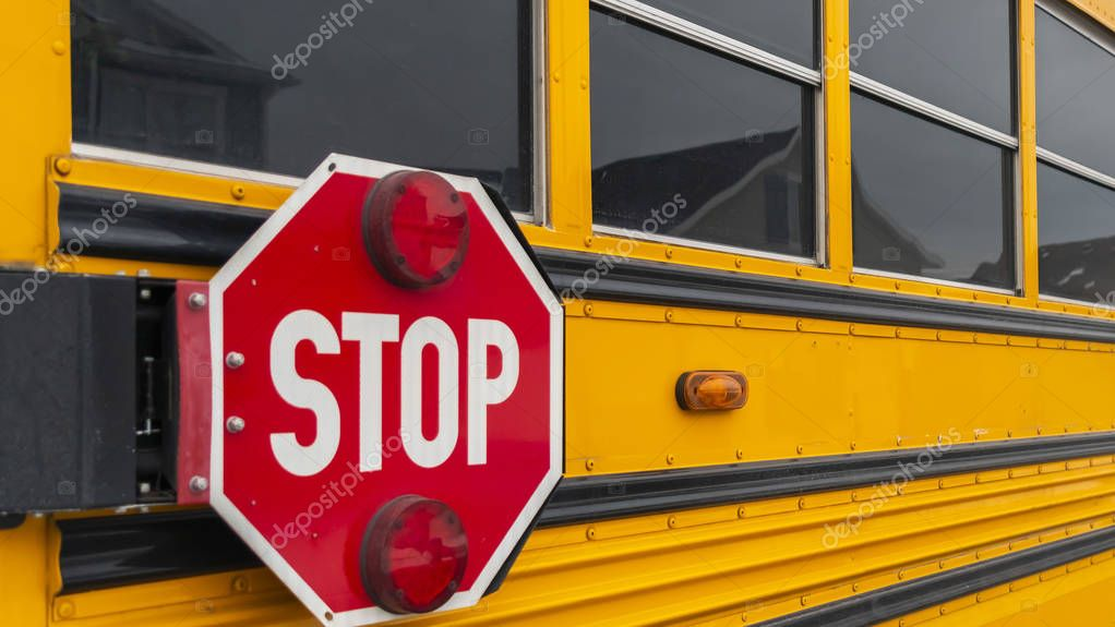 Clear Panorama Exterior view of a yellow school bus with a red stop sign and signal lights