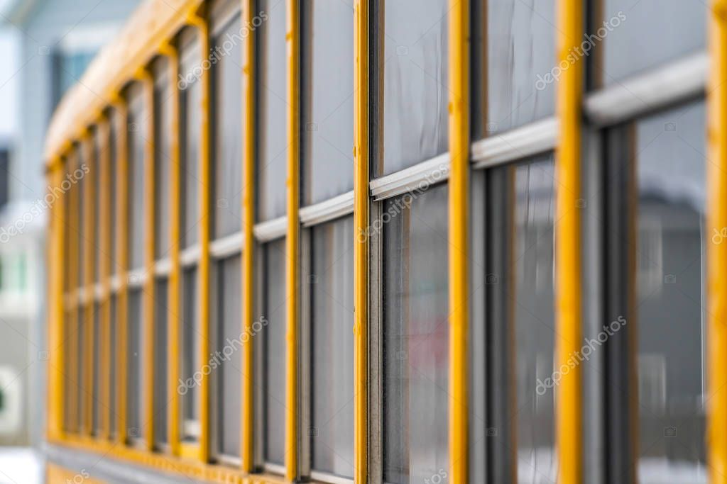 Exterior view of a yellow school bus with a close up on the glass windows
