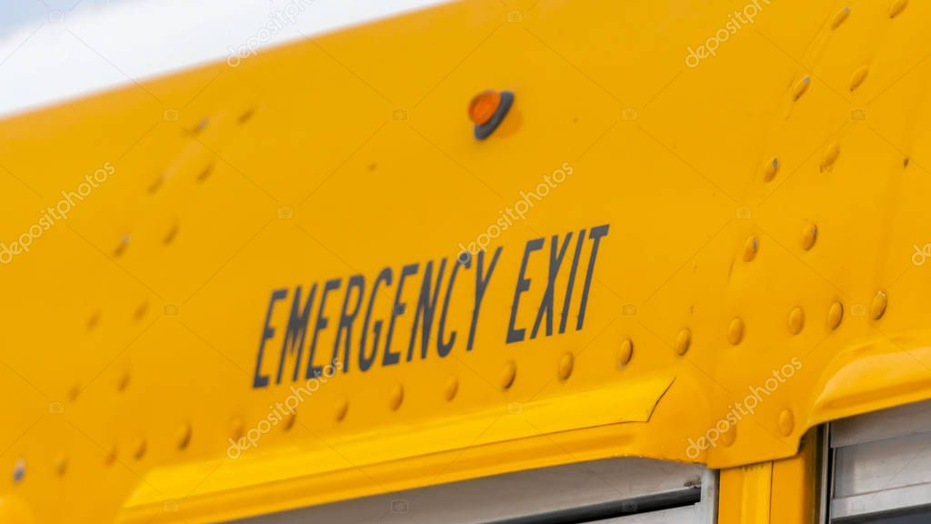 Panorama Close up of the exterior of a yellow school bus with an Emergency Exit sign