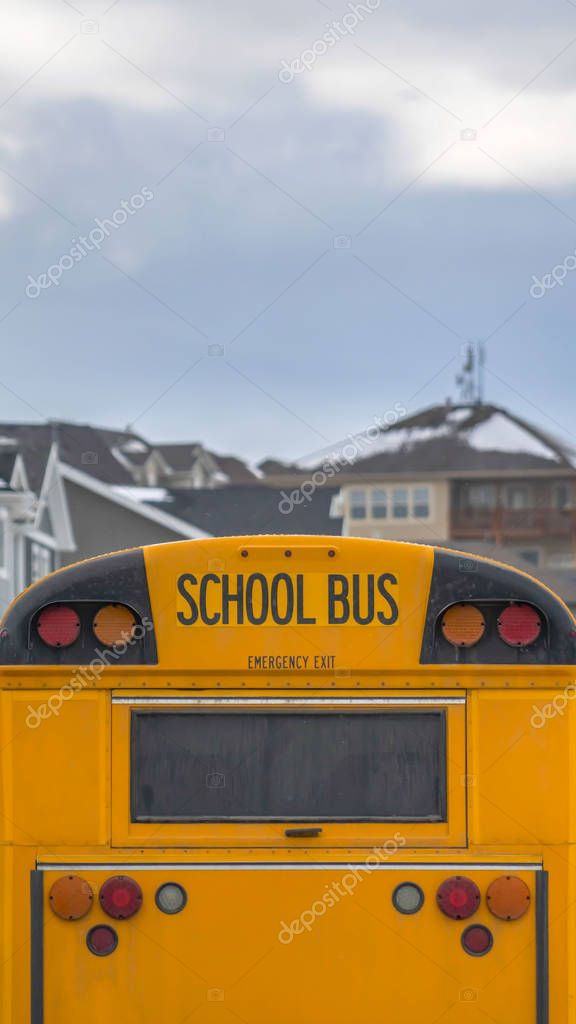 Vertical Yellow school bus with rectangular window and several signal lights at the rear