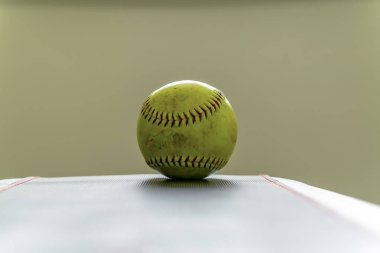 Dirty softball on top of a white table and isolated against a white background