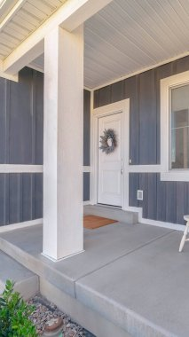 Vertical frame White porch chairs against window and front door of home with gray exterior wall