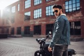 Fotografie Handsome bearded biker with classic style black motorcycle. Cafe racer.