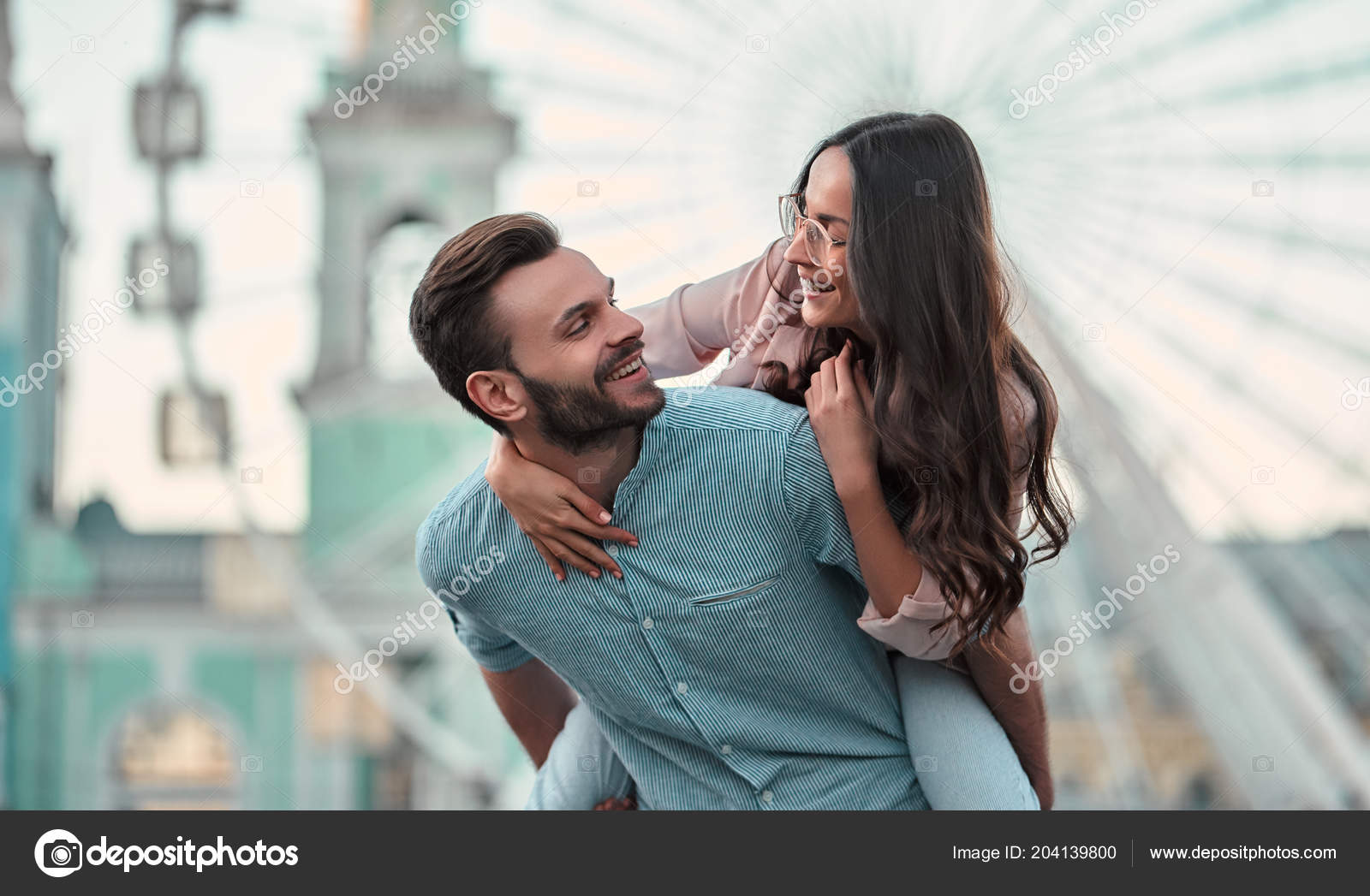 Cute romantic couple spending time together in the city handsome bearded man and attractive young woman are in love hugging kissing and having fun on the