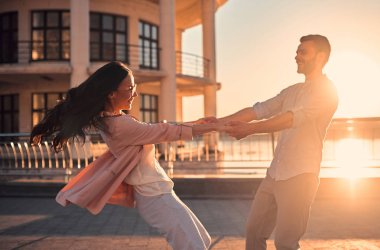 Love is in the air! Cute romantic couple spending time together in the city. Handsome bearded man and attractive young woman are in love. Hugging, kissing and having fun during the sunset.