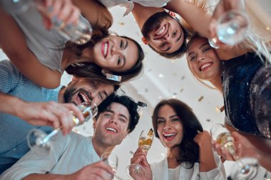Let the party begin! Group of young people having fun together. Dancing in big light room with champagne and confetti falling. Celebrating holiday in big company of close friends.