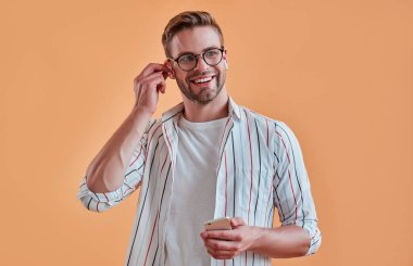 Handsome man isolated. Stylish young man in eyeglasses is  posing with smart phone on orange background. Listening to music using wireless earphones