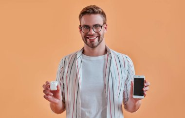 Handsome man isolated. Stylish young man in eyeglasses is  posing with smart phone and wireless earphones on orange background.