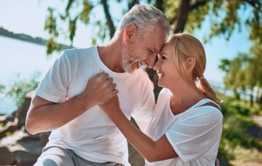 Senior couple is spending time together outdoors. Bearded handsome man and attractive woman are hugging while being in park.