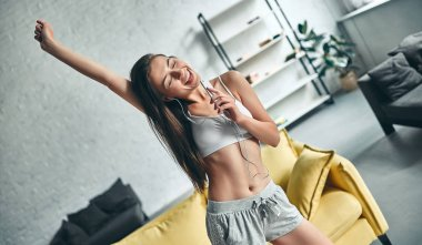 Good morning! Attractive young woman is having rest at home. Girl is having fun and dancing while listening to music in living room.