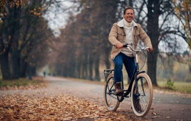 Handsome senior man with bicycle in park in autumn. Active lifestyle concept.