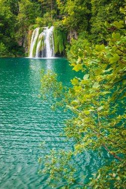 Waterfall at a turquoise lake. The Plitvice Lakes National Park, Croatia, Europe.