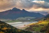 Krajina s horami za mlhavého východu slunce na podzim.