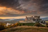 Středověký hrad Beckov v podzimní krajině při západu slunce, Slovensko.