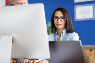 Indecisive young woman in glasses sits at computer