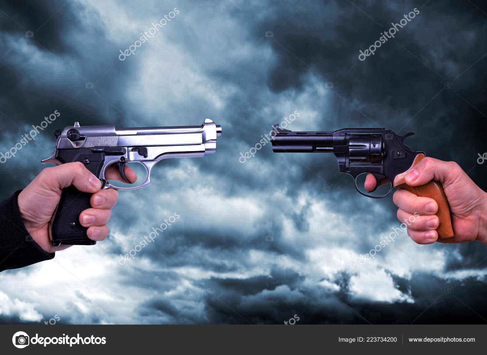 two hand holding gun revolvers background stormy dark sky stock
