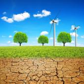 Windräder auf Wiesen und trockenen Flächen mit rissigem Boden. Konzept Klimawandel oder globale Erwärmung.