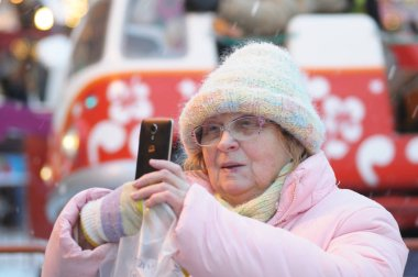Moscow, Russia - 25 December, 2017: An elderly woman with a mobile phone