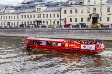 Moscow, Russia, on June 25, 2018. Buildings of the 18th century make an architectural complex of Kadashyovskaya Embankment in a historical part of the city. The walking ship floats down the river.