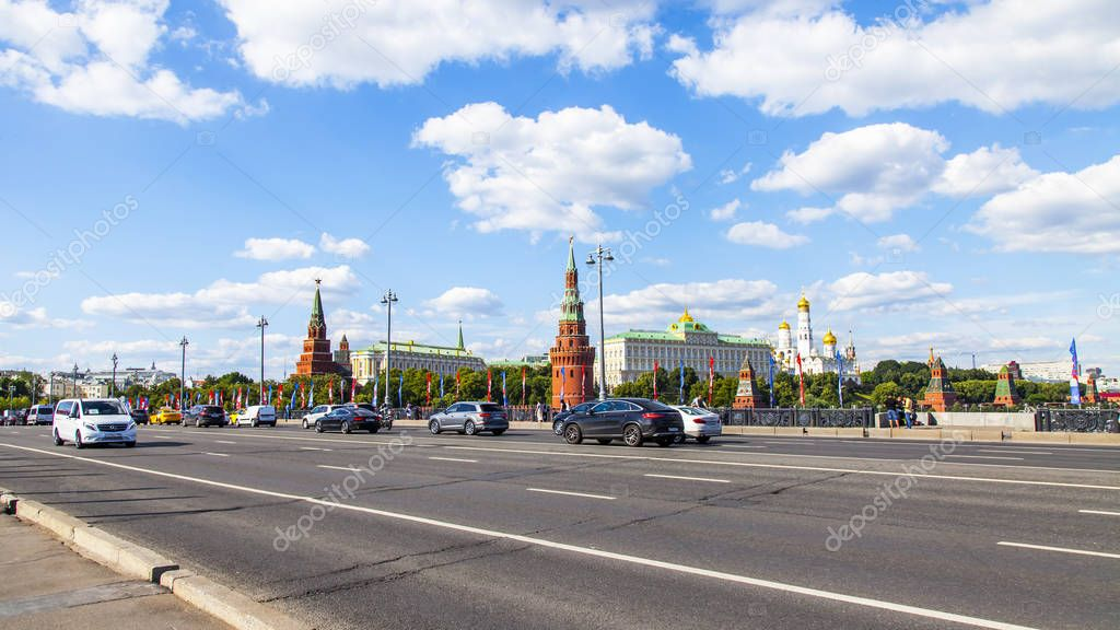 Фотообои Moscow, Russia, on June 25, 2018. Cars go on Big Stone Bridge. Towers of the Moscow Kremlin are visible in the distance