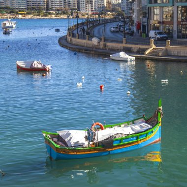 San Giljan, Malta, on January 7, 2019. Walking and fishing boats in the picturesque bay Spinola are lit with the sun in the winter morning. beautiful embankment in the distance