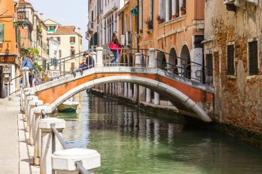 Venice, Italy, on April 25, 2019. The picturesque narrow street with the bridge via the channel. Typical architectural complex of old buildings ashore